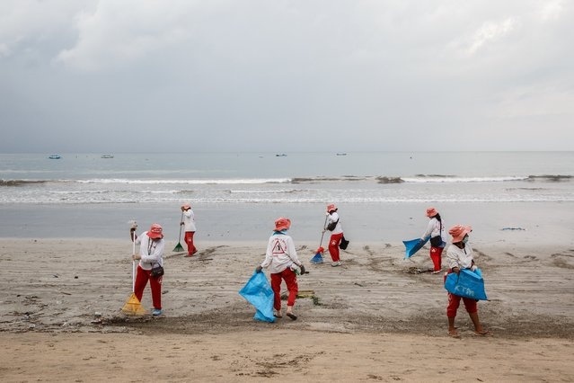 Workers rake up trash along the shore on Kuta Beach, Bali, Indonesia, on Friday, January 22, 2021. Movement restrictions in Bali were extended by two weeks to Feb. 8 as the government sought to curb the spread of coronavirus infections. (Photo by Putu Sayoga/Bloomberg)