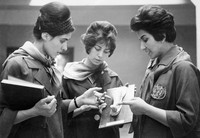 Picture taken in 1962 at the Faculty of Medicine in Kabul of two Afghan medicine students listening to their professor (at right) as they examine a plaster cast showing a part of a human body. (Photo by AFP/Getty Images via The Atlantic)