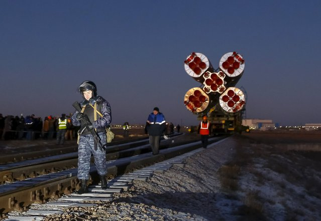 A policeman walks along a railway track ahead of the Soyuz TMA-19M as it is transported from an assembling hangar to its launchpad at the Baikonur cosmodrome, Kazakhstan, December 13, 2015. (Photo by Shamil Zhumatov/Reuters)