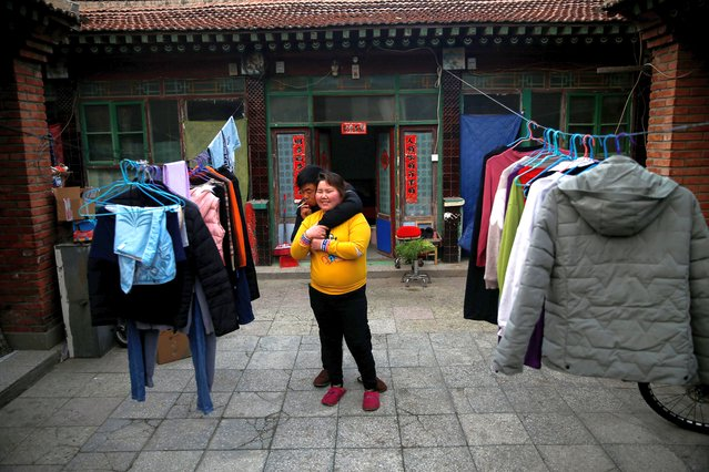 "Yang Nianlian, 33, smokes a cigarette as he embraces his wife Wang Yunxia, 30, in the courtyard by the room that they rent in Majuqiao Town, a suburb of Beijing, China, February 11, 2021. This year, for the first time, the migrant workers are spending the Spring Festival away from their 9-year-old daughter as they heed China's call to stay put, following a spate of coronavirus infections over the winter. ""It doesn't matter where"", Yunxia said. ""When we're together, we're family, we're home"". (Photo by Tingshu Wang/Reuters)"