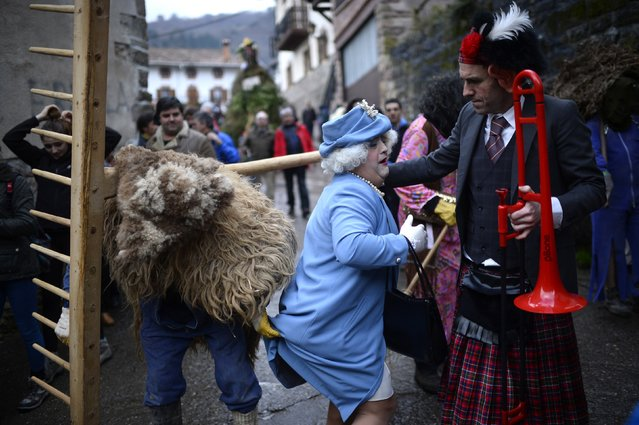 A man lifts the skirt of another dressed as Britain's Queen Elizabeth alongside a man wearing a mask depicting Prince Charles during carnival celebrations in Zubieta January 27, 2015. Bell carrying dancers known as Joaldunak from Zubieta and neighbouring Ituren visit each other's villages performing a ritual dance to ward off evil spirits and awaken the coming spring. (Photo by Vincent West/Reuters)