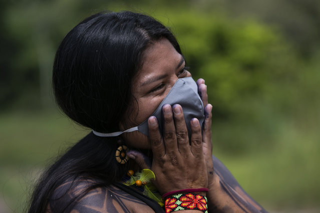 Suzana, a 22-year-old Guarani woman, smiles during an interview in the Mata Verde Bonita village in Marica, Rio de Janeiro state, Brazil, Thursday, February 25, 2021, where healthcare workers are making the rounds with coolers containing doses of China's Sinovac COVID-19 vaccine as part of a mass immunization program aimed at inoculating all of Rio's 16 million residents by the end of the year. (Photo by Bruna Prado/AP Photo)