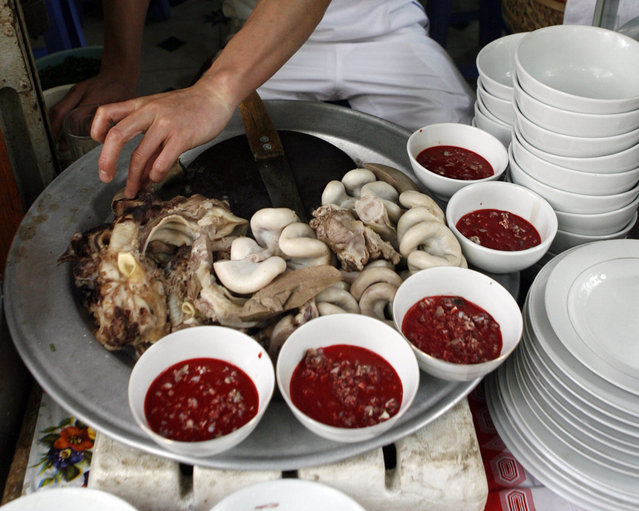 A raw blood dish is displayed with cooked entrails at a restaurant in Hanoi April 28, 2009. Frozen pudding from fresh duck or pig blood is a popular dish in the Southeast Asian country although duck blood is less consumed following bird flu outbreaks that have killed at least 55 Vietnamese since late 2003. In Vietnam, there appeared to be a degree of confusion towards swine flu which is not in fact linked to pigs alone – but an assortment of swine, human and avian viruses. One bowl of raw blood costs VND10,000 ($0.55). (Photo by Reuters/Kham)