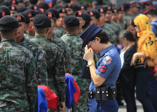 A policewoman wipes her tears as she stands in front of metal caskets containing the bodies of Special Action Force (SAF) police who were killed in Sunday's clash with Muslim rebels, at Villamor Air Base in Pasay city, metro Manila January 29, 2015. (Photo by Romeo Ranoco/Reuters)