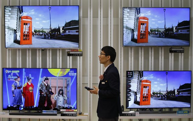 An employee uses his mobile phone in front of LG Electronics' organic light-emitting diode (OLED) TV sets, which are made with LG Display flat screens, at its store in Seoul January 28, 2015. South Korea's LG Display Co Ltd booked its highest quarterly profit in almost four years on Wednesday, buoyed by firm demand for liquid crystal displays (LCD) from television makers and client Apple Inc. (Photo by Kim Hong-Ji/Reuters)