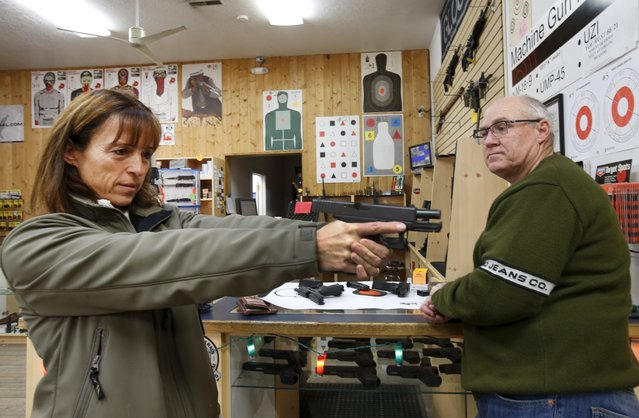 Ulrik Mitchell, (L) tries out a hand gun as her husband Bill, (R) looks on at the Ringmasters of Utah gun range and store, in Springville, Utah on December 18, 2015. (Photo by George Frey/Reuters)