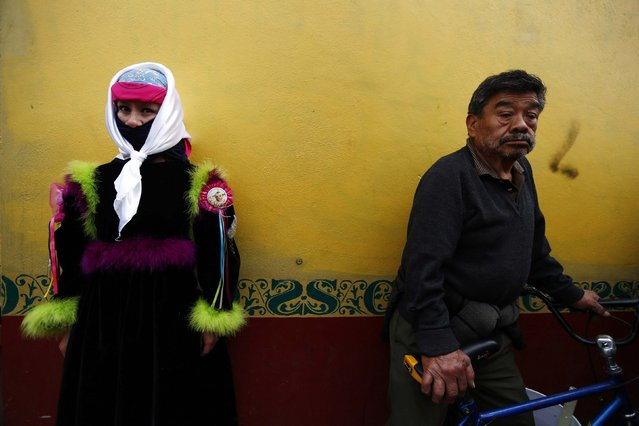 A traditional Chinelo costumed dancer is seen while a man holds his bicycle during a celebration 40 days after the birth of Jesus, in Xochimilco on the outskirts of Mexico City, February 2, 2015. (Photo by Edgard Garrido/Reuters)