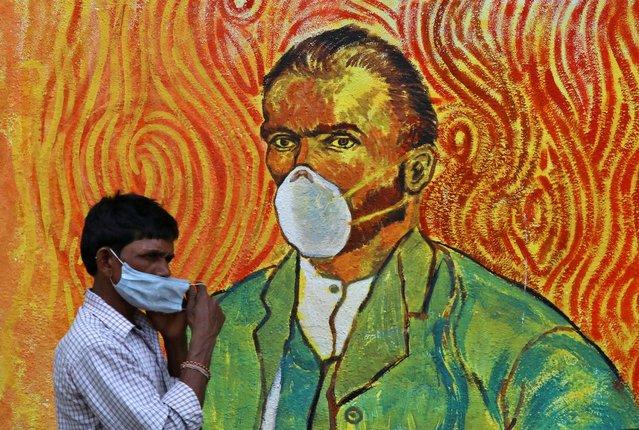 A man adjusts his face mask as he walks past a mural, amidst the spread of the coronavirus disease (COVID-19), in Mumbai, India, March 11, 2021. (Photo by Niharika Kulkarni/Reuters)