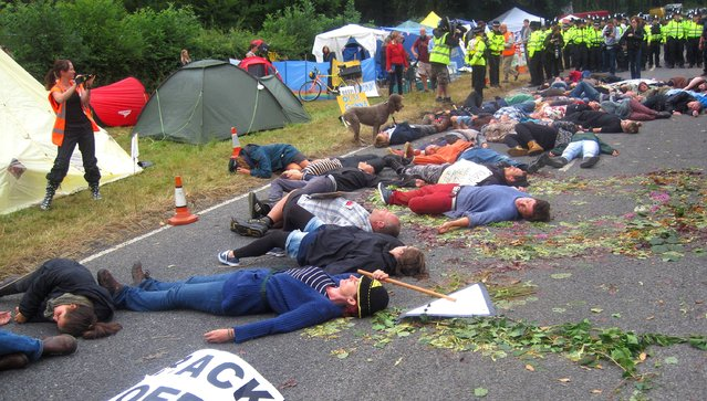 Anti-fracking activists pretending to drop down dead in the middle of the road after a lorry had delivered equipment to a proposed oil exploration drilling site outside Balcombe, West Sussex, on July 31, 2013. (Photo by Tom Pugh/PA Wire)