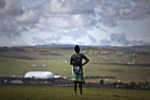 A mourner wearing a banner as a skirt showing the face of South African President Jacob Zuma observes the scene from a hilltop overlooking the burial site of Nelson Mandela in Qunu, South Africa Sunday, December 15, 2013. (Photo by Ben Curtis/AP Photo)