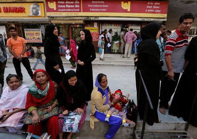 A woman feeds her baby as she and others queue outside a bank to exchange their old high denomination banknotes in Ahmedabad, India, November 17, 2016. (Photo by Amit Dave/Reuters)