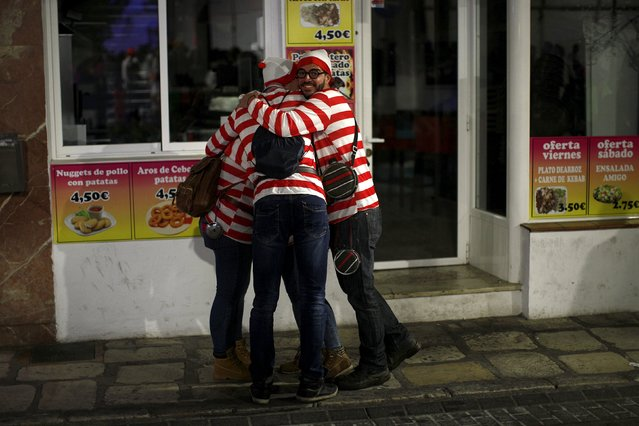 """People dressed up as Wally from the book series """"Where's Wally?"""" embrace as they take part in New Year celebrations in Coin, near Malaga, southern Spain, January 1, 2016. (Photo by Jon Nazca/Reuters)"""