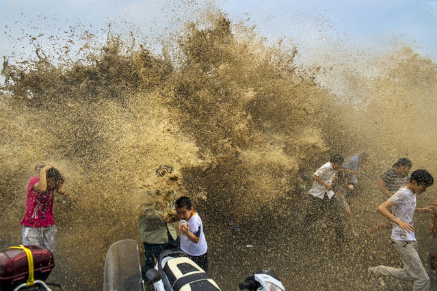 Visitors run away from a tidal bore wave as it surges over a barrier on the banks of Qiantang River, in Hangzhou Zhejiang province, on August 25, 2013. (Photo by Reuters/Stringer via The Atlantic)