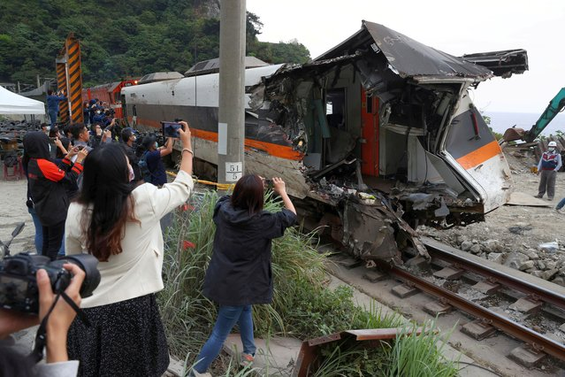 Members of the media document a damaged train carriage extracted from a tunnel after the deadly train derailment north of Hualien, Taiwan on April 6, 2021. (Photo by Ann Wang/Reuters)