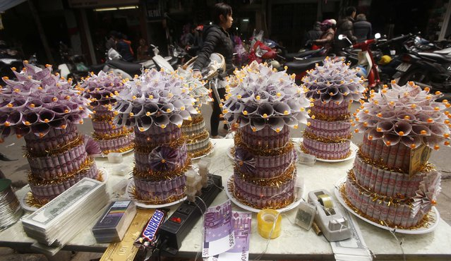 """A woman walks past a table on which decorations made with replica euro and U.S. dollar notes called money trees, are seen for sale on a street in Hanoi February 12, 2015. Money trees, made with replica money, are believed to bring luck to families, and are used to decorate homes during the Vietnamese Lunar New Year festival known as """"Tet"""", which will take place from February 14 to 24. (Photo by Reuters/Kham)"""