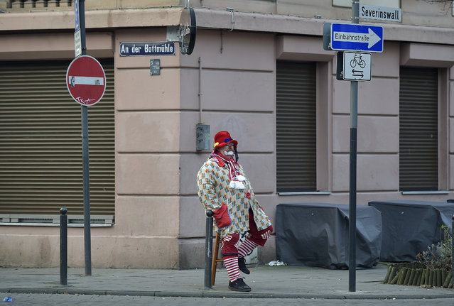 A lonely clown waits alone early morning for the carnival parade in Cologne, western Germany, Monday, February 16, 2015. (Photo by Martin Meissner/AP Photo)