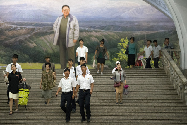 People pass a large picture of Kim Jong-il as they walk through a station on the Pyongyang metro on August 21, 2018 in Pyongyang, North Korea. (Photo by Carl Court/Getty Images)