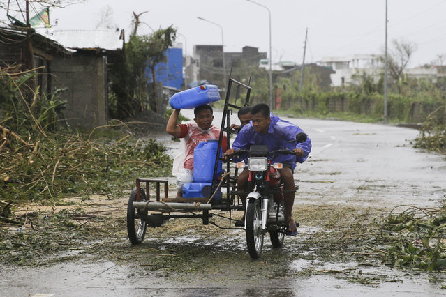 A man uses a water container to shield him from rain brought about by Typhoon Mangkhut as it barreled across Tuguegarao city, Cagayan province, northeastern Philippines, Saturday, September 15, 2018. Philippine officials were assessing damage and checking on possible casualties as Typhoon Mangkhut on Saturday pummeled the northern breadbasket with ferocious wind and rain that set off landslides, damaged an airport terminal and ripped off tin roofs. (Photo by Aaron Favila/AP Photo)