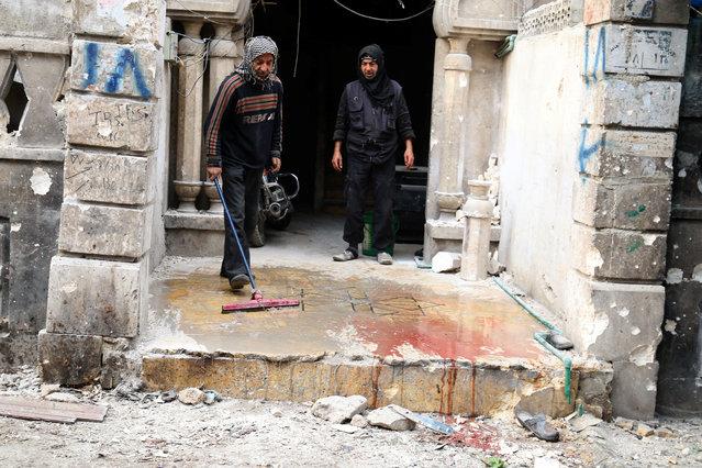 Men wash the blood stained ground after strikes on rebel-held besieged al-Zebdieh district, in Aleppo Syria December 5, 2016. (Photo by Abdalrhman Ismail/Reuters)
