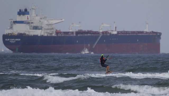 In this Friday, September 29, 2017 photo, a kite surfer glides along the coast as an oil tanker passes in the background, in Port Aransas, Texas. Hurricane Harvey dealt a body blow to the beach town and wiped out the end of the lucrative summer season. Tourists are expected to stay away through the holidays, and even the possibility of getting back to business by spring break looks bleak. (Photo by Eric Gay/AP Photo)