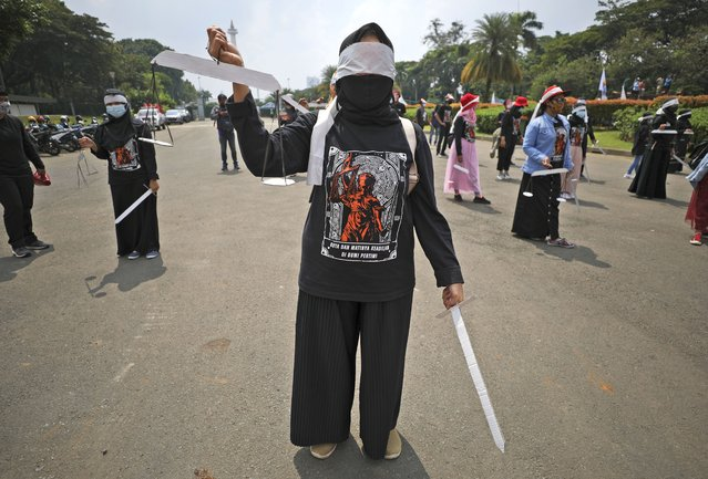 Indonesian workers stand spaced apart as a precaution against coronavirus outbreak, while holding mock sword and scales to symbolize justice during a May Day rally in Jakarta, Indonesia, Saturday, May 1, 2021. Workers in Indonesia marked international labor day on Saturday curtailed by strict limits on public gatherings to express anger at a new law they say could harm labor rights and welfare. (Photo by Dita Alangkara/AP Photo)