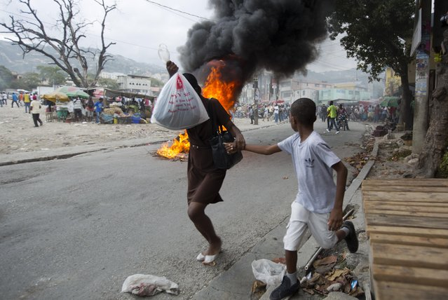 People run past a burning barricade during a street protest after it was announced that the runoff Jan. 24, presidential election had been postponed, in Port-au-Prince, Haiti, Friday, January 22, 2016. (Photo by Dieu Nalio Chery/AP Photo)