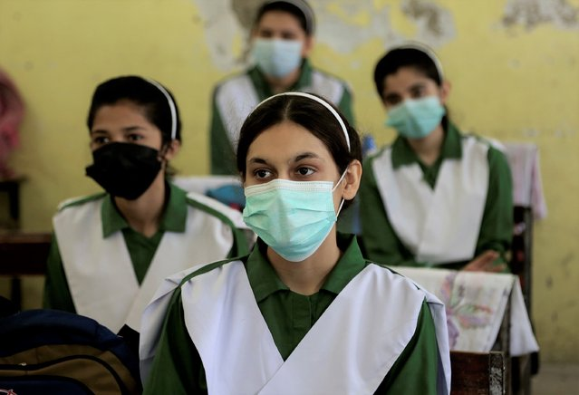 Students wearing face masks to help prevent the spread of the coronavirus attend class at a school, in Peshawar, Pakistan, Tuesday, June 1, 2021. Pakistani authorities reopened schools of grade 10 and 12 following a steady decrease in deaths and infections from the coronavirus. (Photo by Muhammad Sajjad/AP Photo)