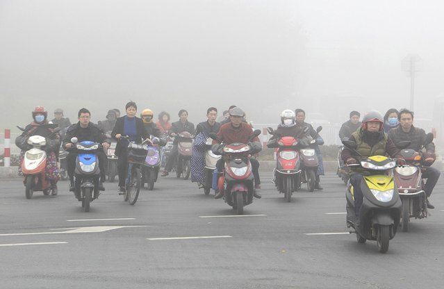 Residents ride their bicycles and electronic bikes to across a street amid thick haze in Shaoxing, Zhejiang province March 17, 2015. (Photo by Reuters/China Daily)