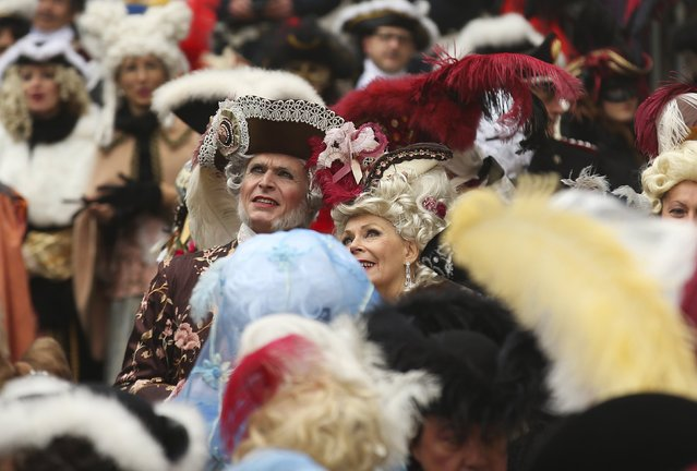 Revellers watch as the traditional Columbine descends from Saint Mark's tower bell on an iron cable during the Venice Carnival, January 31, 2016. (Photo by Alessandro Bianchi/Reuters)
