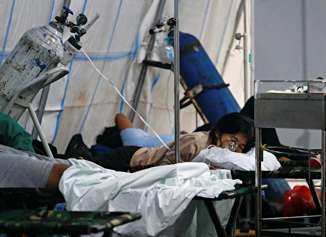A patient suffering from coronavirus breaths with a non-rebreather mask in an emergency tent at a hospital in Jakarta, Indonesia, June 24, 2021. (Photo by Ajeng Dinar Ulfiana/Reuters)