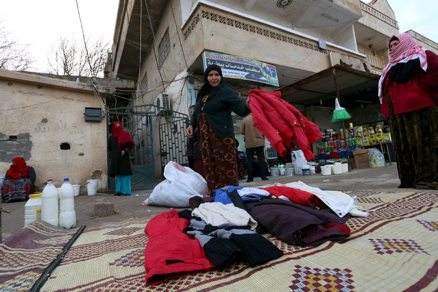 A woman sells used clothes at the Syrian town of Ras al-Ain, close to the Turkish border, January 23, 2016. (Photo by Rodi Said/Reuters)
