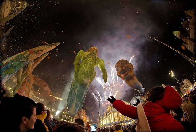 A child stretches out both arms as she watches a show with giant inflatable puppets by French street theater company Les Plasticiens Volant, during an event to mark the start of the Christmas shopping season in Amsterdam, Netherlands, on November 21, 2013. (Photo by Peter Dejong/Associated Press)