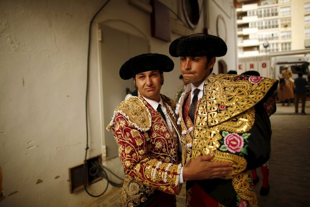 Spanish bullfighters Miguel Angel Perera (R) and Morante de la Puebla embrace each other while waiting for the start of a bullfight at the Malagueta bullring in Malaga, southern Spain, April 4, 2015. (Photo by Jon Nazca/Reuters)