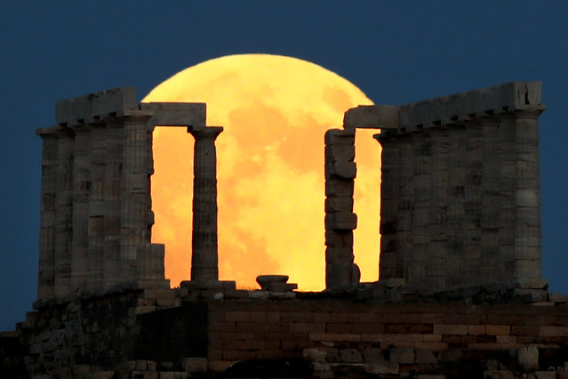 A full moon rises behind the Temple of Poseidon before a lunar eclipse in Cape Sounion, near Athens, Greece, July 27, 2018. (Photo by Alkis Konstantinidis/Reuters)