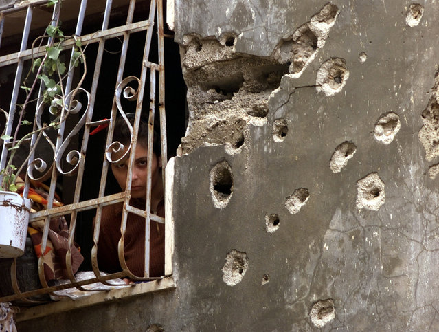 A Palestinian woman looks from her house hit by heavy machine gunfire from Israeli troops in Al Azza refugee camp opposite the Paradise Hotel in Bethlehem, October 2001. (Photo by Desmond Boylan/Reuters)