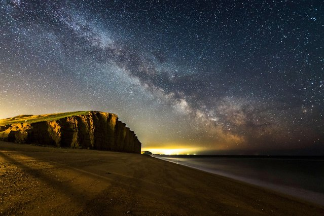The Milky Way over West Bay on Dorset's Jurassic coast in United Kingdom on April 15, 2021. (Photo by Graham Hunt/Alamy Live News)