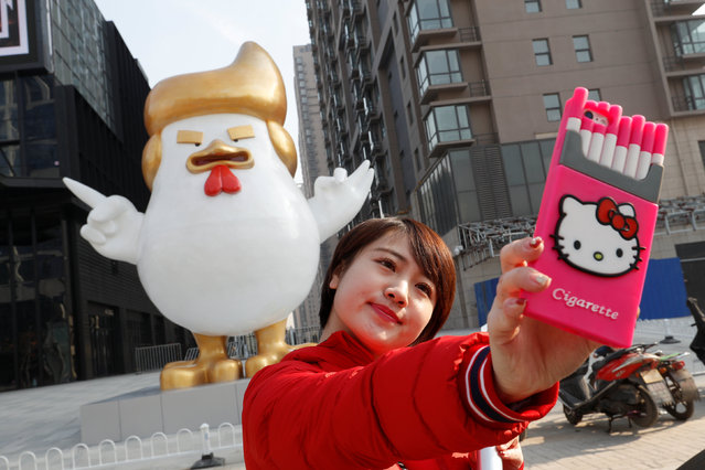 A woman takes a selfie in front of a sculpture of a rooster that local media say bears resemblance to U.S. President-elect Donald Trump, outside a shopping mall in Taiyuan, Shanxi province, China December 30, 2016. (Photo by Jon Woo/Reuters)