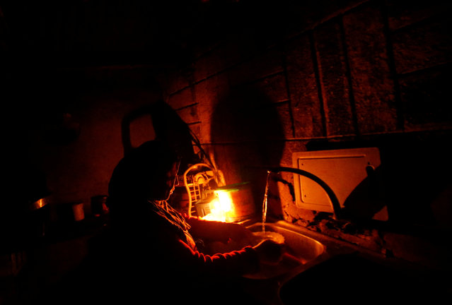 A Palestinian woman uses a candle light as she washes up in her kitchen during a power cut inside her house in Beit Lahiya in the northern Gaza Strip January 11, 2017. (Photo by Mohammed Salem/Reuters)
