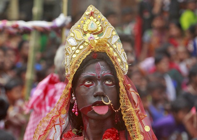 A devotee dressed as Hindu goddess Kali performs during a ritual as part of the annual Shiva Gajan religious festival at Pratapgarh, on the outskirts of the northeastern Indian city of Agartala, April 14, 2015. (Photo by Jayanta Dey/Reuters)