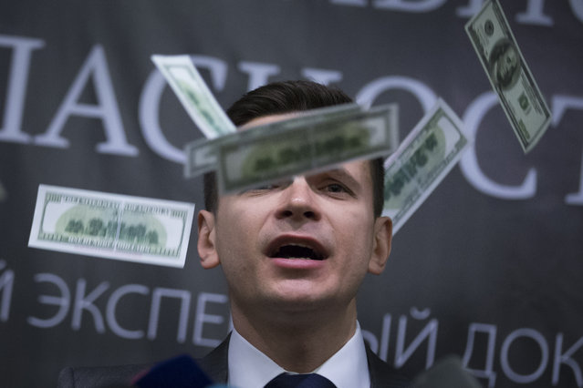Russian opposition activist Ilya Yashin speaks while fake banknotes thrown at him by protesters, as Yashin presents a report on Chechen leader Ramzan Kadyrov, in Moscow, Tuesday, February 23, 2016. Yashin released a report accusing Moscow-backed Chechnya's regional leader, Ramzan Kadyrov, of involvement in the killing of Russian opposition leader Boris Nemtsov and other alleged crimes. (Photo by Alexander Zemlianichenko/AP Photo)