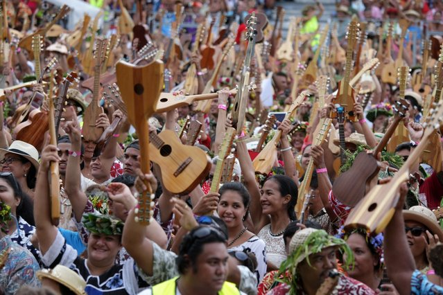 People try on April 11, 2015 to beat the world record of ukelele players at the first Tahiti Ukulele Festival in Papeete with more than 4,750 participants from all the islands of the French Indian Ocean archipelago. The largest ukulele ensemble was set in July 2014 with 2,370 participants in Southampton. (Photo by Gregory Boissy/AFP Photo)