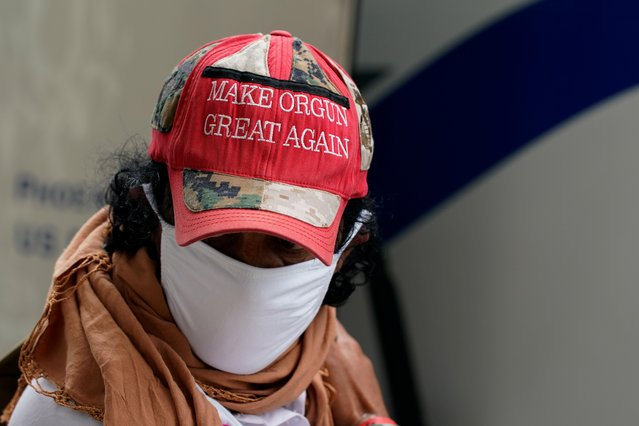 """A man wearing a hat that reads """"Make Orgun Great Again"""" boards a bus taking him and other Afghan refugees to a processing center upon arrival at Dulles International Airport in Dulles, Virginia, U.S., August 29, 2021. (Photo by Elizabeth Frantz/Reuters)"""