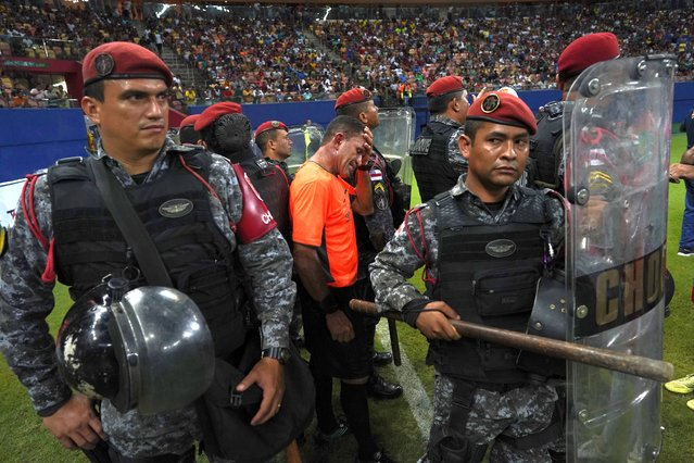 Police protect referee Moacir Eriberto Guedes during the Peladao final amateur soccer tournament at Arena da Amazonia in Manaus, Brazil, Saturday, February 16, 2019. Players in the men's final invaded the pitch each time they disagreed with the referee, coaches made hand signals suggesting the linesman was a thief, homophobic insults came fast and furious and ten riot police were on hand to protect referees from violence in three occasions. (Photo by Victor R. Caivano/AP Photo)