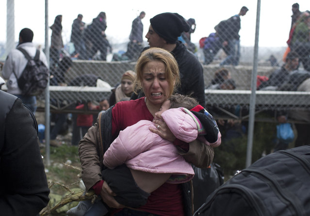 A woman carries a child on the Greek side of the border as they run away after Macedonian police fired tear gas at a group of the refugees and migrants who tried to push their way into Macedonia, breaking down a border gate near the northern Greek village of Idomeni on Monday, February 29, 2016. (Photo by Petros Giannakouris/AP Photo)
