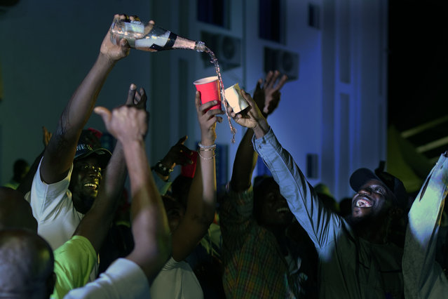 Supporters of Incumbent President Muhammadu Buhari pour champagne anticipating a win as they wait for the results to be officially announced in Abuja, Nigeria, Tuesday, February 26, 2019. Anxious Nigerians on Tuesday awaited a second day of state-by-state announcements of presidential election results in a race described as too close to call. Buhari is facing opposition presidential candidate Atiku Abubakar. (Photo by Jerome Delay/AP Photo)