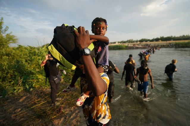 Migrants, many from Haiti, cross the Rio Grande from Del Rio, Texas, to return to Ciudad Acuna, Mexico, Tuesday, September 21, 2021, to avoid deportation from the U.S.  The U.S. is flying Haitians camped in a Texas border town back to their homeland and blocking others from crossing the border from Mexico. (Photo by Fernando Llano/AP Photo)