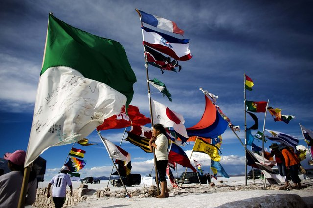 A girl stands next to flags from around the world left by travelers at the Uyuni Salt Flats. (Photo by Victor R. Caivano/Associated Press)