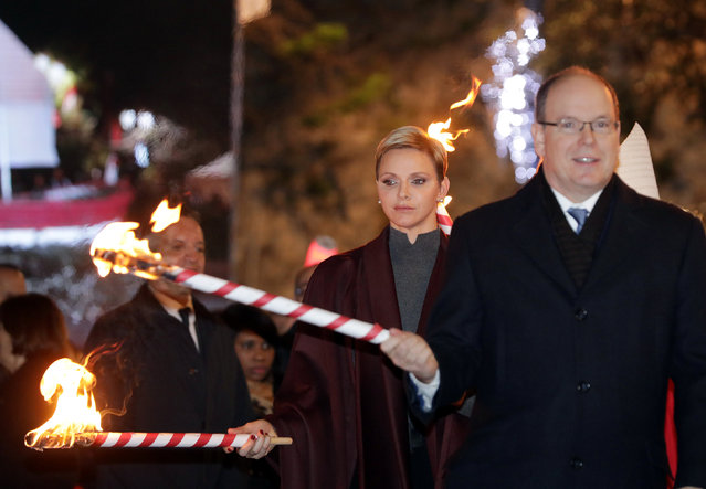 Prince Albert II of Monaco (R) and his wife Princess Charlene (L) hold a torch to burn a small fisherman's boat during the traditional Saint Devota celebration in Monaco, January 26, 2017. (Photo by Eric Gaillard/Reuters)