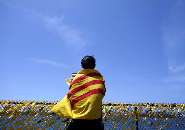 The flag of former South Vietnam is draped over the shoulders of Vietnamese refugee Bai-Binh Ton-Thap as he prays next to some of the 58,300 yellow ribbons tied to a fence surrounding the flight deck of the USS Midway as the ship commemorates the 40th Anniversary of Operation Frequent Wind and the fall of Saigon in San Diego, California, United States  April 26, 2015. (Photo by Mike Blake/Reuters)