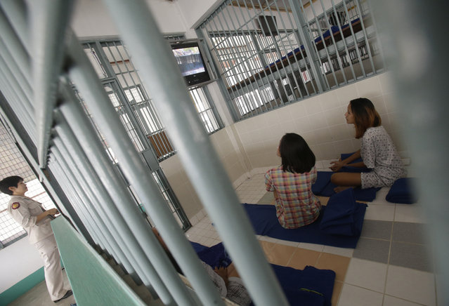 In this January 6, 2017 photo, a female officer locks a cell as transgender inmates watch TV at Pattaya Remand Prison in in Pattaya, Chonburi province, Thailand. The prison separates lesbian, gay, bisexual and transgender prisoners from other inmates, a little-known policy despite being in place nationwide since 1993, according to the Department of Corrections. (Photo by Sakchai Lalit/AP Photo)
